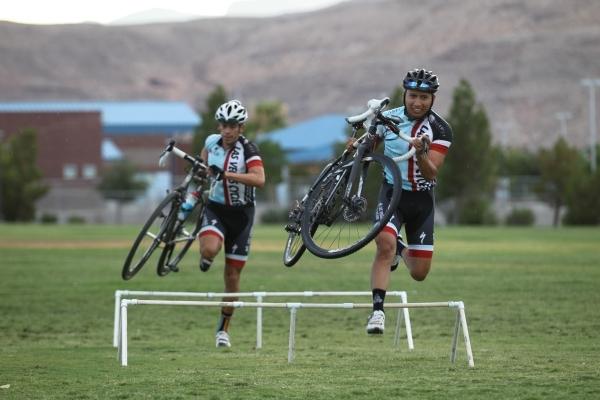 Las Vegas Cyclo-Cross member Mark Smith, right, jumps over an obstacle while warming up at Red Ridge Park, near Durango Road and Arby Avenue. The group plans to compete in the UCI World Cup event  ...