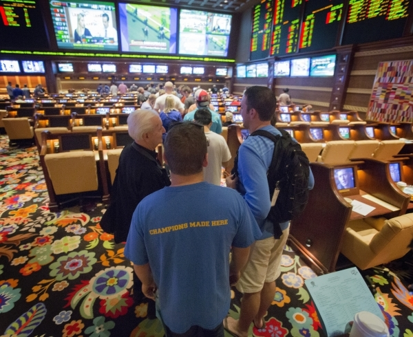 Bettors stand in line at Wynn Race and Sports Book during NCAA Men's basketball tournament  on Friday, March 21, 2014. March Madness betting is expected to generate a sports book handle of $ ...
