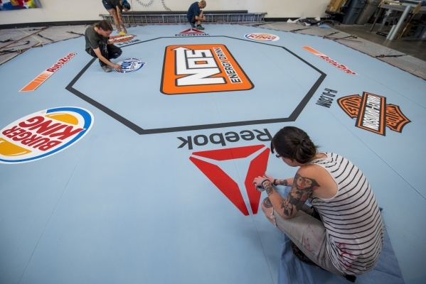 Camille Bohannon, bottom, makes finishing touches to a UFC mat at Larger Than Life, Inc. in Las Vegas on Wednesday, July 29, 2015. (Joshua Dahl/Las Vegas Review-Journal)