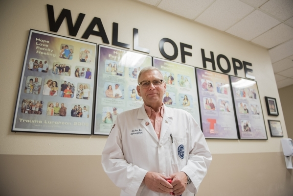 Dr. John Fildes, medical director for the Department of Trauma Services at University Medical Center, stands near the Wall of Hope, showing lives the facility has saved. (Martin S. Fuentes/Las Veg ...