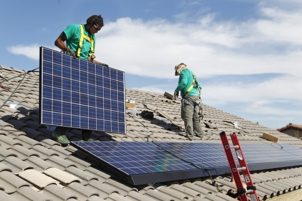 Solar City installation crew leader Greg Kates, left, and Guillermo Aviles install solar panels on a North Las Vegas home. Proponents say a green bank would make financing more readily available f ...