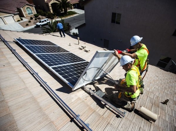 Jacy Sparkman, left, and Matt Neifeld with  Robco Electric install solar panels at a home in northwest Las Vegas. Proponents say a green bank would  make money more readily available to finance pr ...