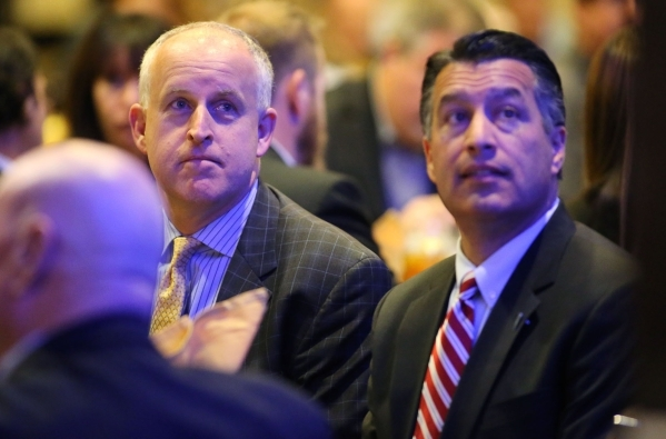 Tesla executive Diarmuid O'Connell, left, and Gov. Brian Sandoval listen to a speaker at the Governor's Business Conference at the Atlantis Resort Casino in Reno on Tuesday, Aug. 25, 2 ...
