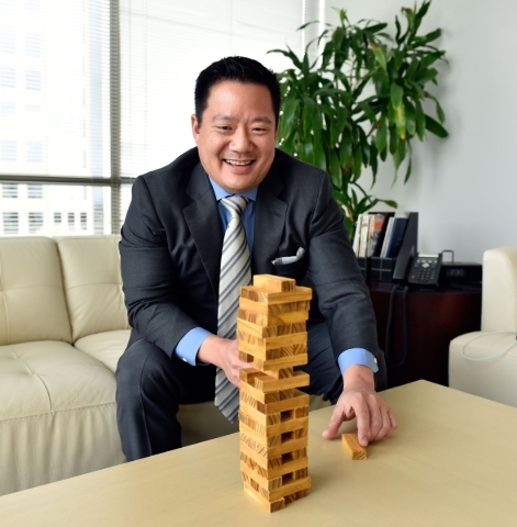 Kai-Shing Tao, CEO of Remark Media, plays the game Jenga while sitting his Las Vegas office on Tuesday, Aug. 25, 2015. Remark Media, a digital media company focusing on the 18- to 34-year-old age  ...