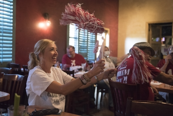 From left, Leea Myers, Jeff Martin, Maggie Vann and Bill Walley watch the University of Alabama vs. University of Louisiana Monroe game during the University of Alabama alumni football watch party ...