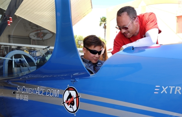 """Eric """"Bumblebee"""" Lawrence, right, shows the controls to the Extra 330LC to Jiefu He at Sky Combat Ace located at the Henderson Executive Airport, Thursday, July 31, 2014. SCA pairs up pa ..."""