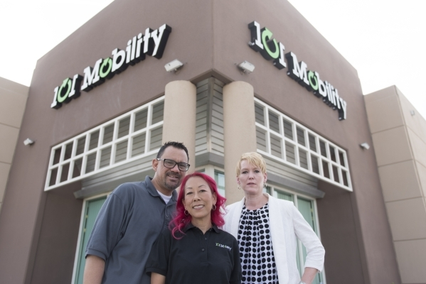 Business consultant with FranNet, Sarah Brown, right, poses with co-owners of a 101 Mobility franchise, Michele Kim-Andres, center, and Ed Andres outside of the Andres' store in Las Vegas Mo ...