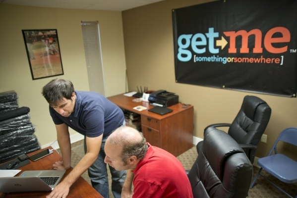 Matt Krueger, left, walks potential independent contractor Simon Swinton through paperwork during a recruitment event for Get Me, a new ridehail company. Daniel Clark/Las Vegas Business Press