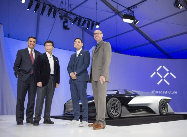 Nevada Gov. Brian Sandoval, left, stands for a photo with Faraday Future executives Richard Kim, head of global design, Ding Lei, co-founder, global vice chairman See Plan, LETV and Nick Sampson,  ...