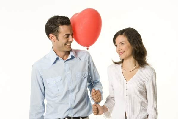 Young couple holding heart-shaped balloon and looking at each other