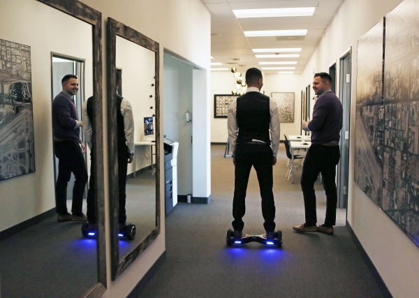 Kamran Zand, owner and broker at Luxury Estates International, center, moves through the office on a Hoverboard at Luxury Estates International Thursday, Feb. 4, 2016, in Las Vegas. The real estat ...