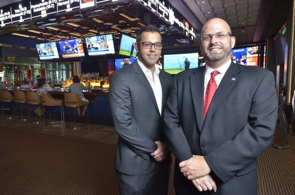Parikshat Khanna, COO of CG Technology, left, and Brian Benowitz, senior vice president of casino operations at the Cosmopolitan hotel-casino, are shown in the new Race and Sports Book at the Cosm ...