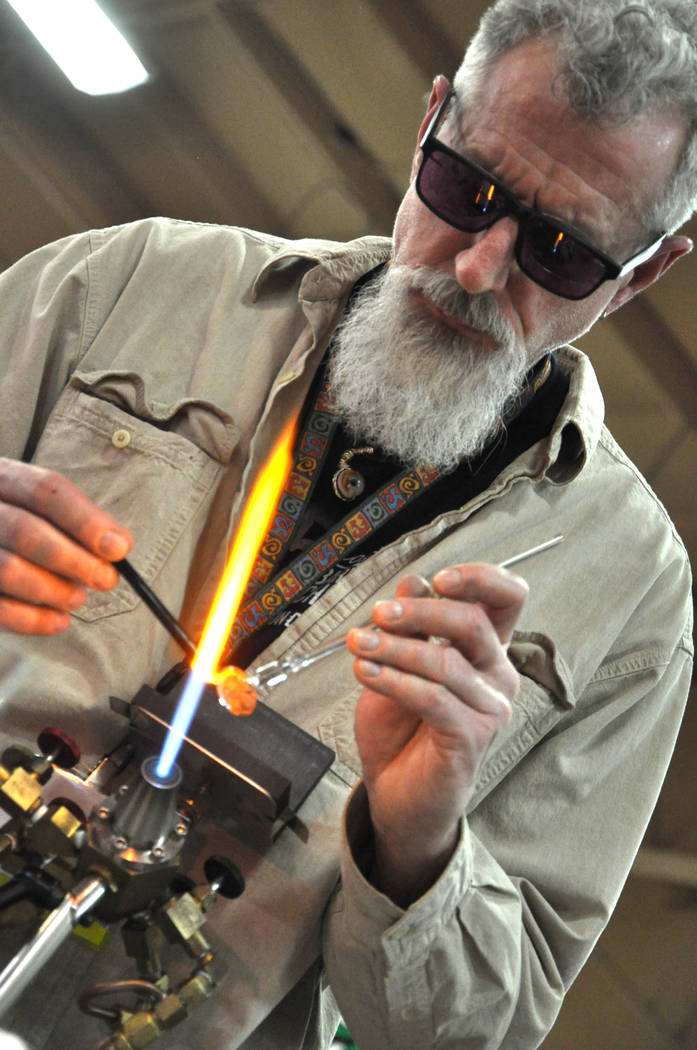 Jess Caserta from the Carlisle School of Glass Art in Millville, New Jersey, gives a flameworking demonstration at the Glass Craft and Bead Expo, Mar. 29-Apr. 2 at the South Point Hotel and Casino ...