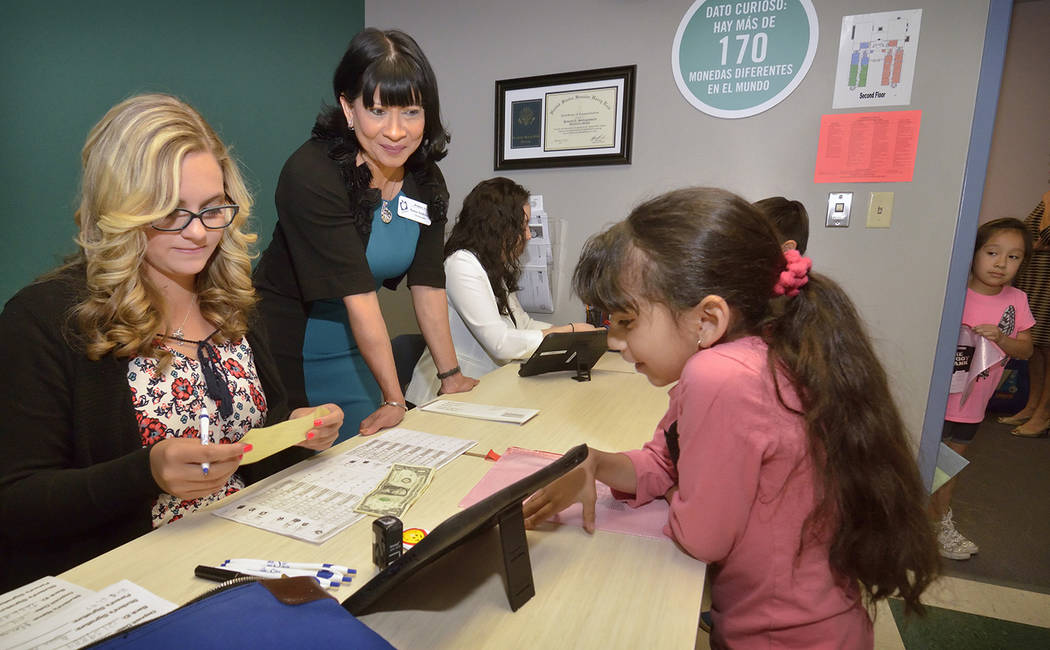 Sonia Anderson, founder and CEO of Andson, Inc., center, and teller Emilee Savage, left, help first-grader Claudia Chaves with a deposit at the Piggy Bank in Howard E. Hollingsworth Elementary Sch ...
