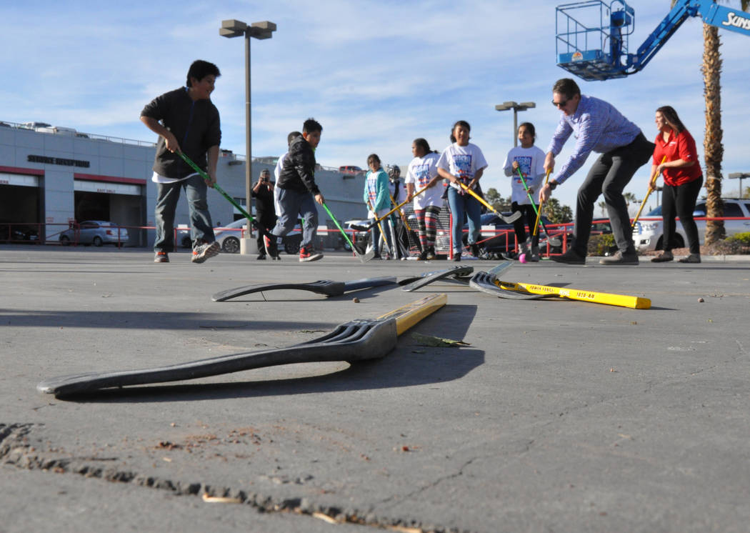 Murray Craven, right and forward, senior vice president of the Vegas Golden Knights and former National Hockey League center, plays street hockey with children from After-School All-Stars Mar. 7 a ...