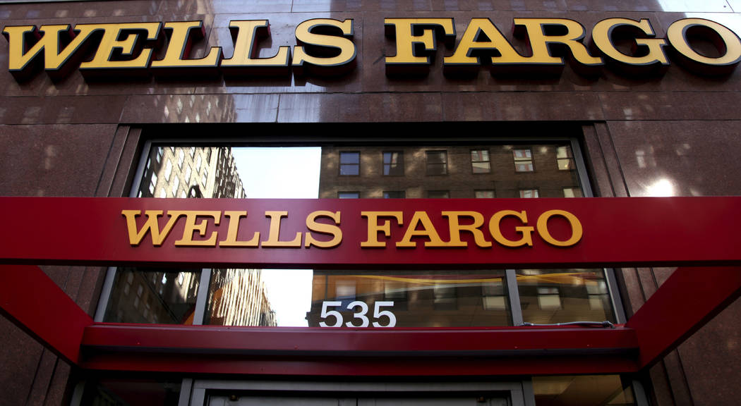 In this May 6, 2012, file photo, a Wells Fargo sign is displayed at a branch in New York. The San Francisco-based bank has extended its general banking agreement with the state of Nevada. (AP Phot ...