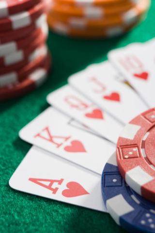 Playing cards making royal flush in hearts by poker chips (close up/selective focus)