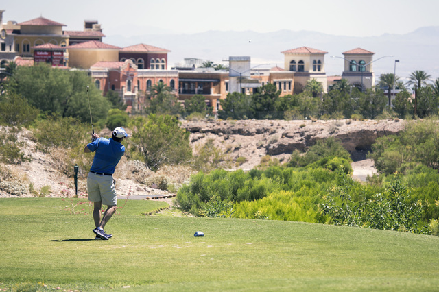 A golfer tees off at Badlands Golf Course July 15. In the background is Tivoli Village. (Jeff Scheid/The Las Vegas Business Press)