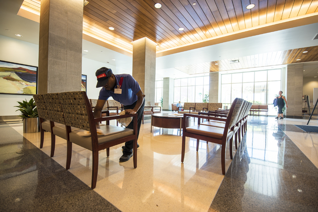 Alex Johnson wipes down chairs at Centennial Hills Hospital Medical Center in Las Vegas. Alex is part of a development program with Opportunity Village to help people with disabilities transition  ...