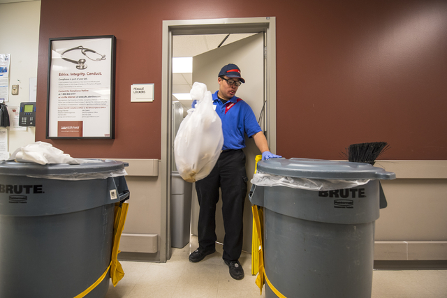 Travis Easler-Shaw empties trash cans at Centennial Hills Hospital Medical Center in Las Vegas on Wednesday, June 3, 2015. Travis is part of a development program with Opportunity Village to help  ...