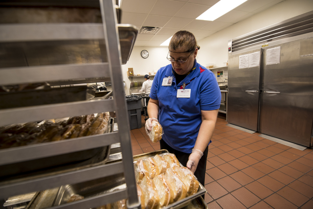 Michelle Santos places sandwiches on a tray at Centennial Hills Hospital Medical Center in Las Vegas on Wednesday, June 3, 2015. Michelle is part of a development program with Opportunity Village  ...