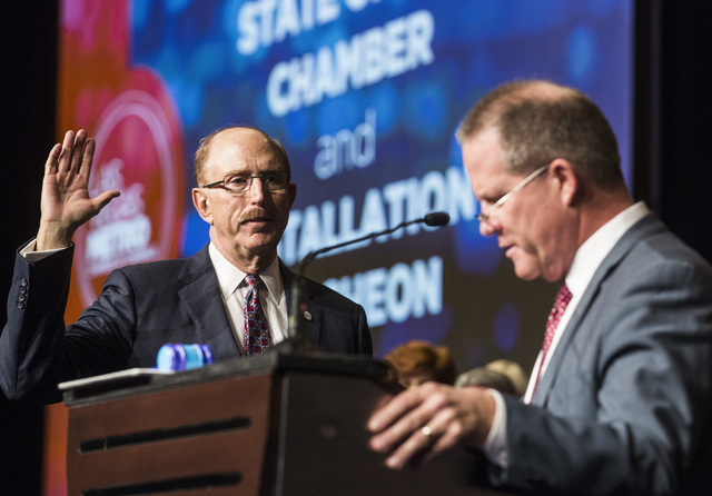 Bill Noonan, incoming chairman of the Las Vegas Metro Chamber of Commerce, takes the oath off office while Nevada Lt. Gov Mark Hutchison conducts a swearing-in ceremony at Cosmopolitan on Thursday ...