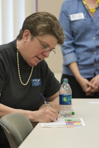 Lori Murphy, chapter chair of SCORE fills out a Girl Scout Cookies order form during a presentation about the business of Girl Scout Cookies and the Girl Scouts CEO in Training program at the Urba ...