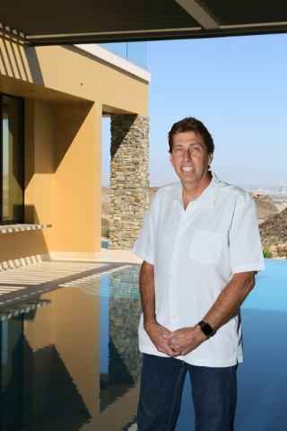 Daniel Coletti, president of Sun West Custom Homes, stands in the grand covered patio with an infinity pool overlooking the valley at an under-construction luxury home Tuesday, June 2, 2015, in He ...