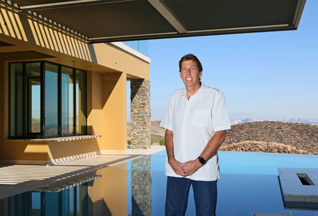 Daniel Coletti, president of Sun West Custom Homes, stands in the grand covered patio with an infinity pool overlooking the valley at an under-construction luxury home in Henderson. The 12,000-squ ...
