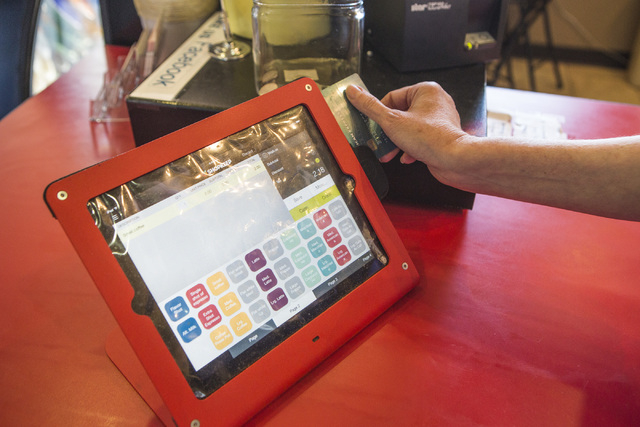 Owner Linda Ray swipes a credit card at Avery's Coffee,9440 W Sahara Ave on Friday, April 3, 2015. Small businesses are facing a major expense in upgrading their credit card readers ahead of an Oc ...