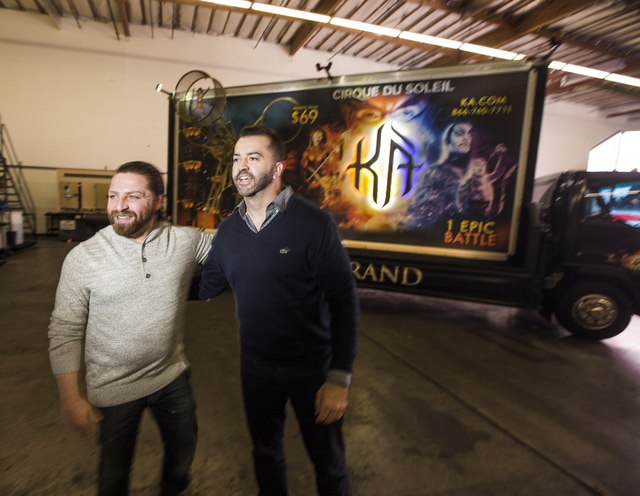 "Managing partners Shaun Habibian, left, and Jeremie Watkins stand in front of a custom 3D build-out mobile billboard for ""KÀ"" by Cirque du Soleil in a warehouse at Kre8 Media Outdoor Advertis ..."