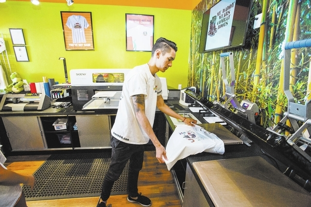 Graphic designer Zach McKee presses a T-shirt inside Big Frog Custom T-Shirts & More. (Jeff Scheid/Las Vegas Business Press)