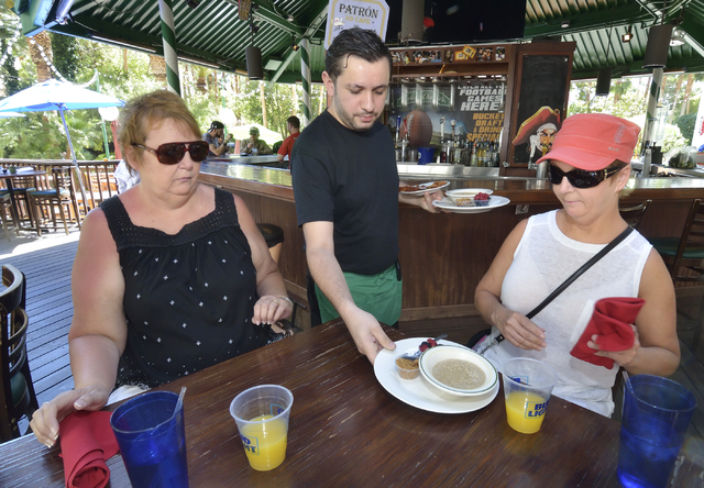 Can Turkmen, center, serves breakfast to sisters Kym Hargrove, left, and Cathy Janney at Carlos'n Charlie's in the Flamingo hotel-casino at 3555 Las Vegas Blvd. South in Las Vegas on Friday, May 2 ...