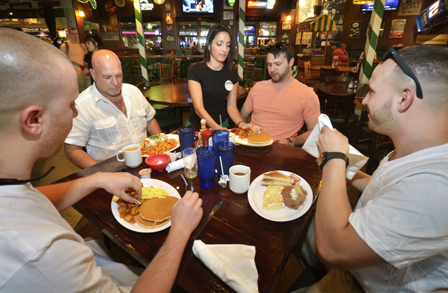 Denise Espitia, center, serves breakfast to, from left, Ryan Allen, and Chuck Cole, Mike Orfanos and Charlie Cole at Carlos'n Charlie's in the Flamingo hotel-casino at 3555 Las Vegas Blvd. South i ...