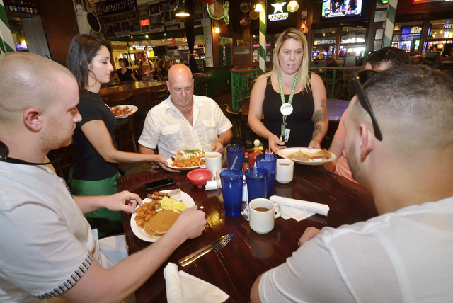 Denise Espitia, second from left, and Dani Cipriano, second from right, serve, from left, Ryan Allen, and Chuck and Charlie Cole at Carlos'n Charlie's in the Flamingo hotel-casino at 3555 Las Vega ...
