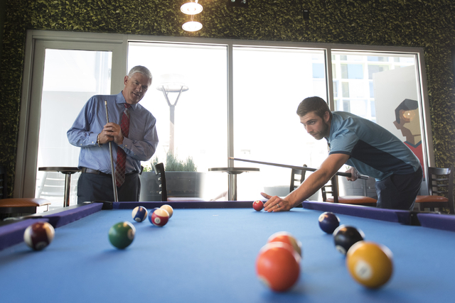 Mark Kelly, vice president of casino operations with Bally's, Paris and Planet Hollywood, left, and his son, Ryan Kelly, pool operations manager at The Linq Hotel, play a game of pool in the recre ...