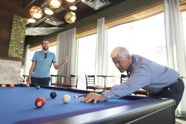 Mark Kelly, vice president of casino operations with Bally's, Paris and Planet Hollywood, right, and his son, Ryan Kelly, pool operations manager at The Linq Hotel, play a game of pool in the recr ...