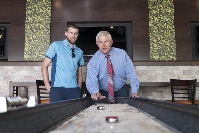 Mark Kelly, vice president of casino operations with Bally's, Paris and Planet Hollywood, right, and his son, Ryan Kelly, pool operations manager at The Linq Hotel, play a game of shuffleboard in  ...