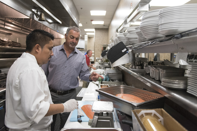 Jason Ogulnik/Las Vegas Business Press Gino Ferraro, right, speaks with Martin Bautista as Bautista prepares salmon at Ferraro's Italian Restaurant & Wine Bar in Las Vegas.