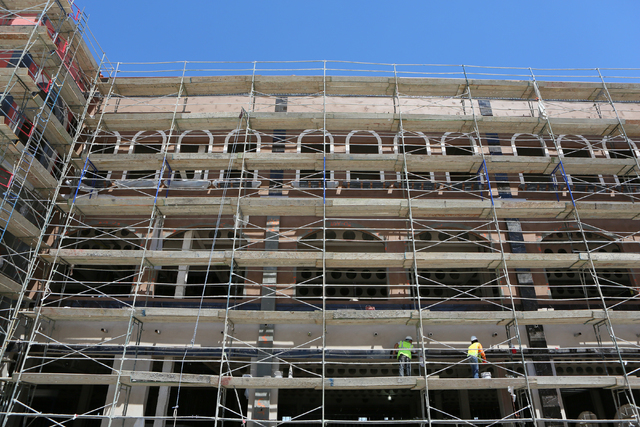 Workers install natural stone on an exterior of a building at Tivoli Village's second phase. The mixed-use shopping, office and dining center is slated to open in October. (Ronda Churchill/Las V ...