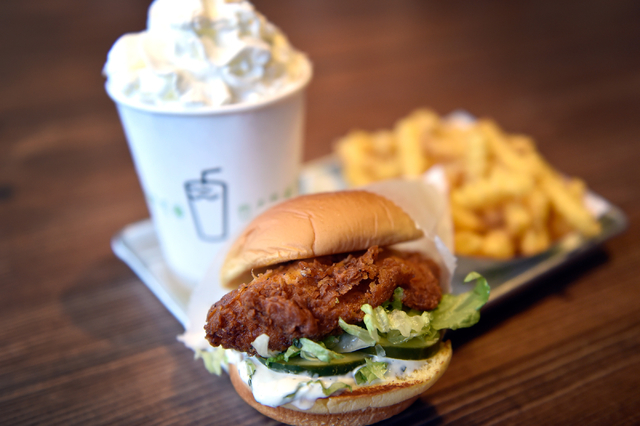 A Chick'n Shack sandwich meal with crinkle cut french fries and a whipped-cream topped chocolate shake is seen at the Shake Shack restaurant at the New York-New York hotel-casino Monday, May 2, 20 ...