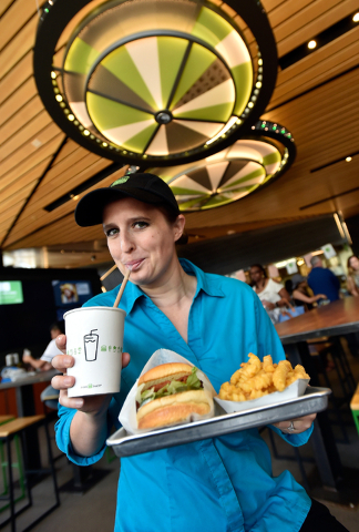 Restaurant manager Michelle Stripp sips a chocolate shake as she displays a Chick'n Shack sandwich with crinkle-cut french fries at the Shake Shack location at the New York-New York hotel-casino M ...