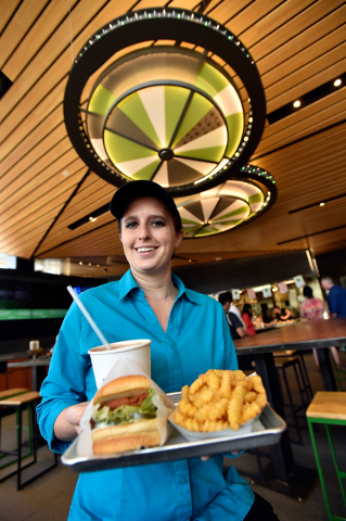 Restaurant manager Michelle Stripp displays a Chick'n Shack sandwich with crinkle-cut french fries and a chocolate shake at the Shake Shack location at the New York-New York hotel-casino Monday, M ...