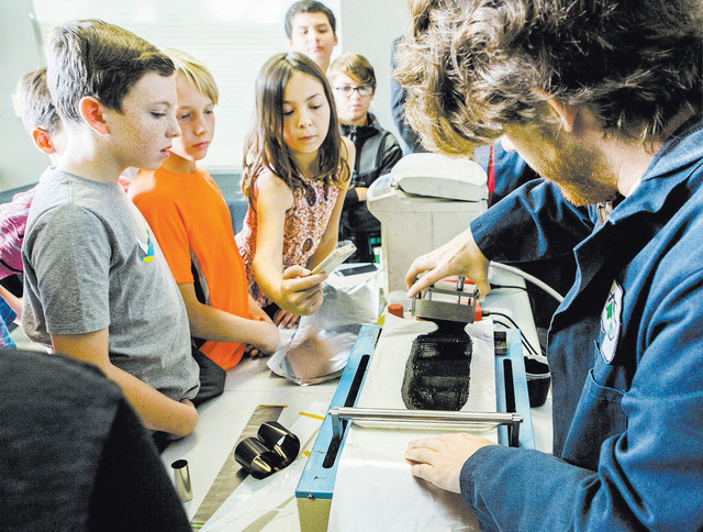 Chemical engineer Harley Haskins, right, shows elementary students how to make a lithium battery during a tour, Wednesday, Oct. 5, 2016, at K2 Energy Solutions located at 7461 Eastgate Road in Hen ...