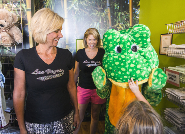 Robyn Brewington,left, and Lisa Hughes smile while a child touches Frogger the mascot inside Big Frog Custom T-Shirts & More at the Southern Highlands Marketplace. (Jeff Scheid/Las Vegas Busin ...