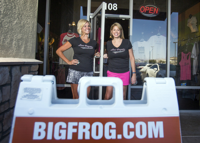Robyn Brewington, left, and Lisa Hughes stand for a photo outside Big Frog Custom T-Shirts & More at the Southern Highlands Marketplace Aug. 9. They launched the business in June. (Jeff Scheid ...