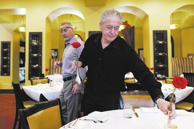 Virgilio Ferraro, right, places roses on tables at Ferraro's Italian Restaurant & Wine Bar in Las Vegas, Thursday, Aug. 25, 2016.  Gino Ferraro, looks on. Jason Ogulnik/Las Vegas Review-Journal