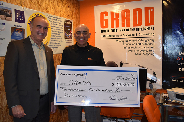 Scott Aney (left), Nevada regional executive for City National Bank, presents Reza Karamooz, CEO of GRADD, with a $2,500 donation to fund ongoing research and education programs related to the dro ...