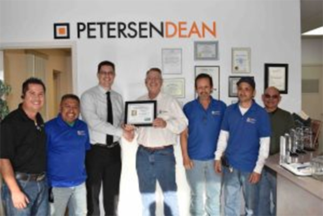 Todd Schultz, chief administrator for the Safety Consultation and Training Section, presents Steve Howard, senior vice president Las Vegas, and the PetersenDean Team with Safe Partner Award. (Cour ...