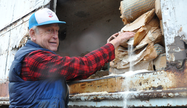 R.C. Farms owner Robert Combs secures organic corn meal as part of his pigs' diets. The farm will close in early January to make way for the housing development, Sedona Ranch. Photo by Buford Davi ...